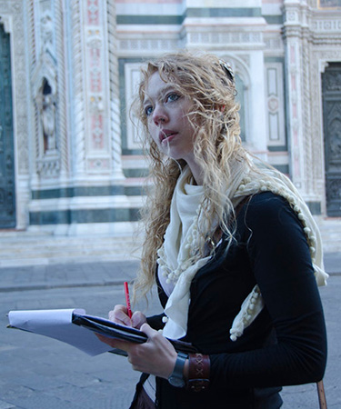 Photo of student walking and writing in Florence