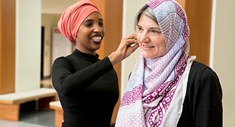 Image of a student helping a faculty member properly wear a hajib