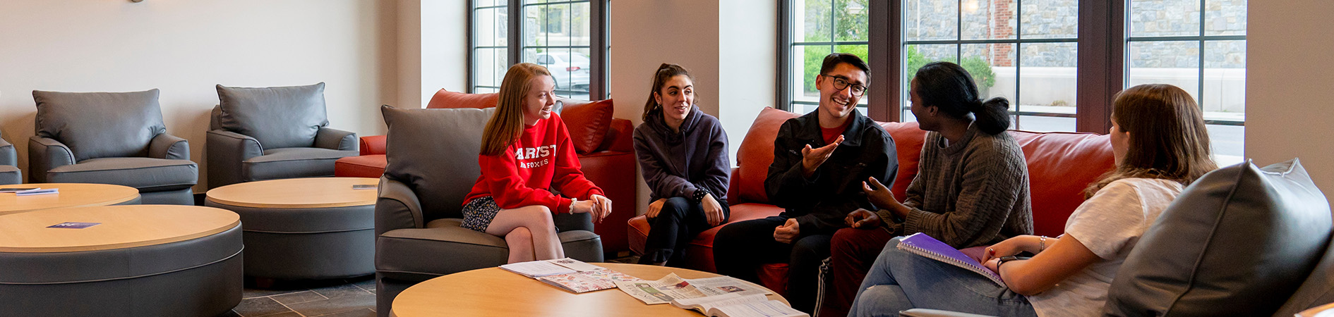Photo of students socializing in residence hall lounge area