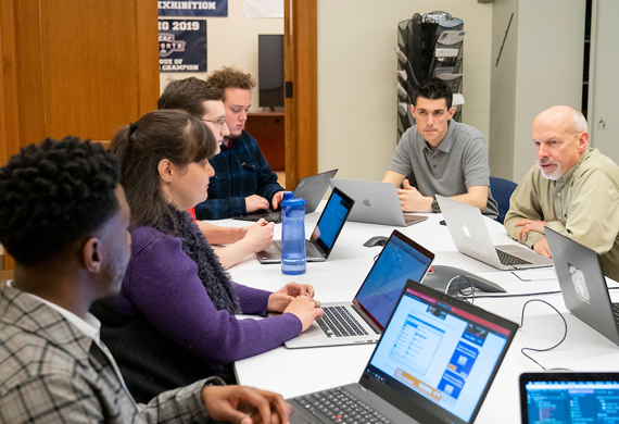 Image of faculty and a group of students collaborating.